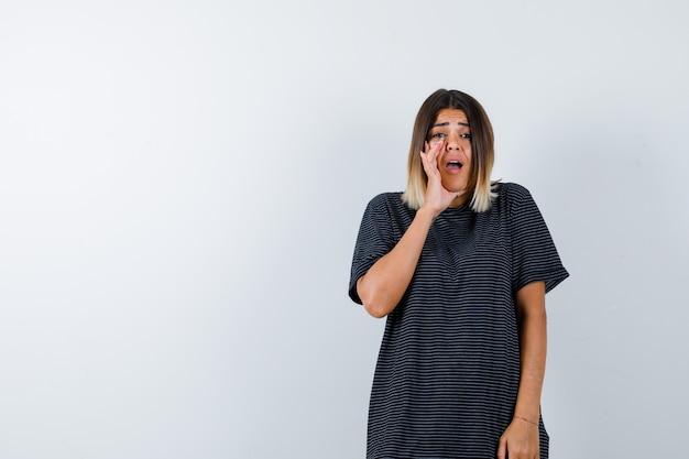Retrato de uma senhora contando um segredo por trás das mãos em uma camiseta preta e parecendo preocupada com a vista frontal