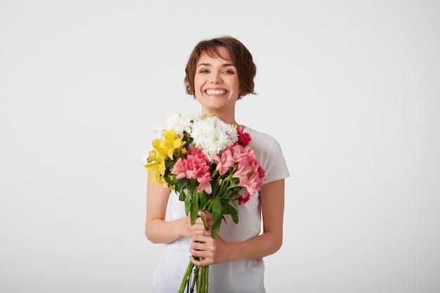 Retrato de uma senhora de cabelos curtos simpática sorridente em t-shirt branca em branco, segurando um buquê de flores coloridas, muito feliz e sorrindo sobre uma parede branca.