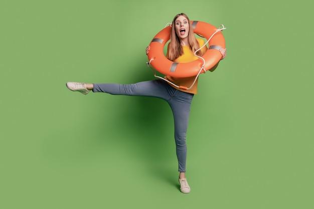 Retrato de uma senhora descuidada e descolada segurando a dança do círculo inflável e usar uma camiseta jeans amarela sobre fundo verde