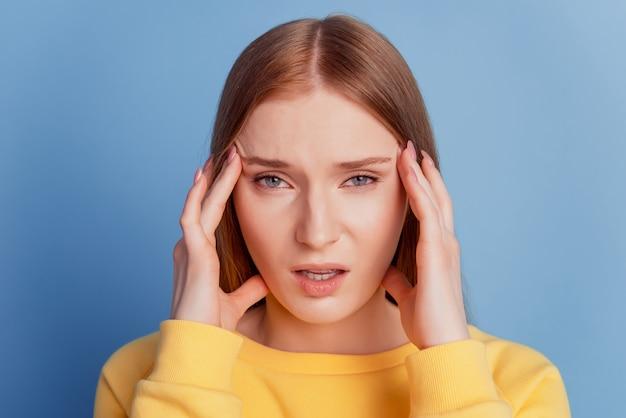 Retrato de uma senhora doente exausta, dor de cabeça nas têmporas, sensação de indisposição sobre fundo azul