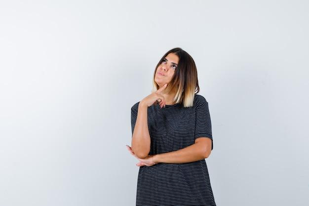 Retrato de uma senhora em pé em uma pose pensativa com uma camiseta preta e uma vista frontal sonhadora