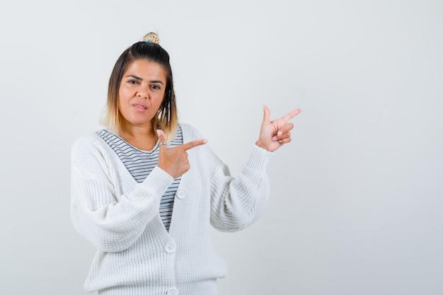 Retrato de uma senhora encantadora apontando para o canto superior direito em uma camiseta, cardigã e parecendo sensata