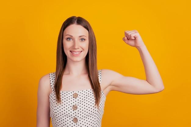 Retrato de uma senhora encantadora poderosa levantando a mão e mostrando os bíceps em fundo amarelo