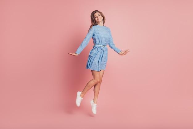 Retrato de uma senhora feminina pulando com tênis vestido curto