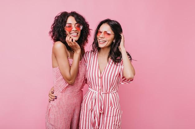 Retrato de uma senhora incrivelmente bonita com pele escura, de óculos cor de rosa. modelos dos estados unidos se abraçam e sorriem lindamente.