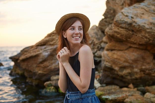 Retrato de uma senhora jovem de sardas de gengibre positivo no chapéu, amplamente sorri e aproveitar a manhã à beira-mar, parece alegre e feliz.
