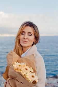 Retrato de uma senhora linda em pé e imaginando algo à beira-mar durante o dia.