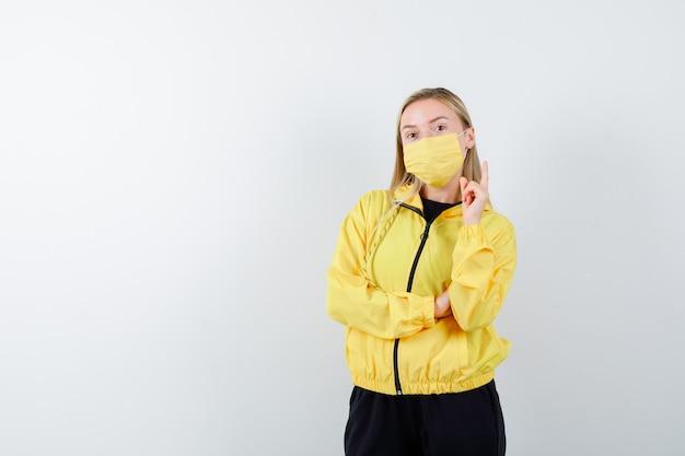 Retrato de uma senhora loira apontando para cima com agasalho, máscara e olhando a vista frontal inteligente