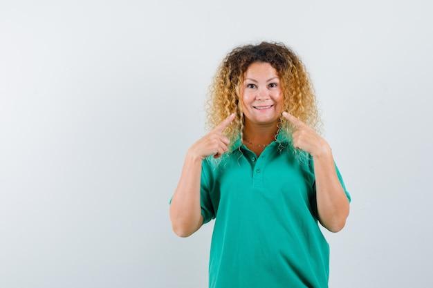Retrato de uma senhora loira e bonita apontando para o seu sorriso em uma camiseta polo verde e com uma vista frontal jovial