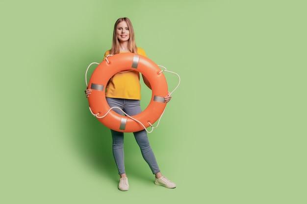 Retrato de uma senhora loira encantadora segurando um círculo inflável e usando tênis jeans camiseta amarela sobre fundo verde