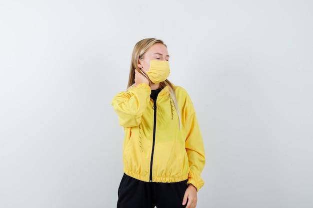Retrato de uma senhora loira sofrendo de dor no pescoço com agasalho, máscara e parecendo vista frontal cansada