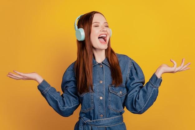 Retrato de uma senhora louca e animada usando fones de ouvido, ouvindo música e cantando de boca aberta sobre fundo amarelo