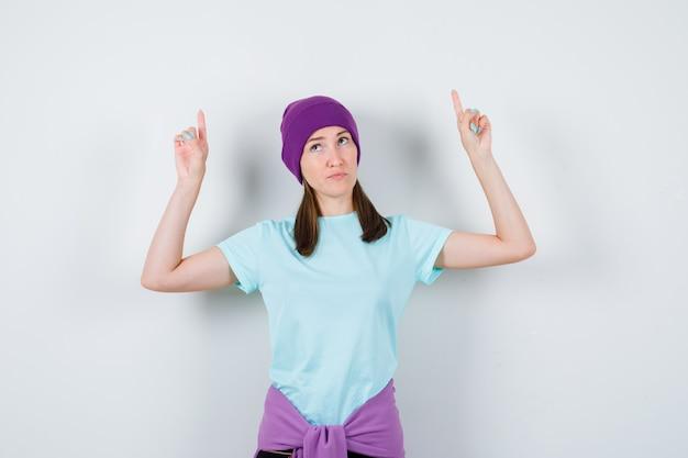 Retrato de uma senhora maravilhosa apontando para cima com uma blusa, um gorro e olhando de frente com confiança