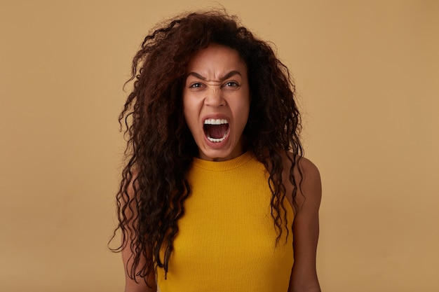 Retrato de uma senhora morena de cabelos castanhos encaracolados com raiva, gritando loucamente enquanto olha para a câmera e mantendo as mãos abaixadas enquanto posa sobre um fundo bege