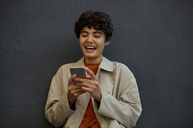 Retrato de uma senhora morena elegante positiva com cabelo curto, segurando o smartphone nas mãos e olhando para a tela alegremente, lendo artigos engraçados, vestida com roupa da moda