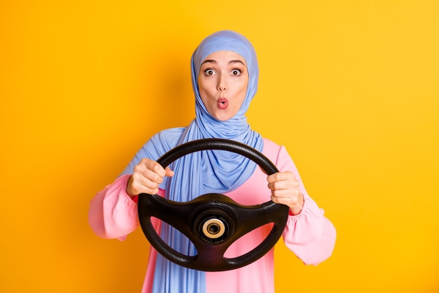 Retrato de uma senhora muslimah muito engraçada e divertida, usando um hijab, segurando o leme de turing isolado em um fundo de cor amarela vívida