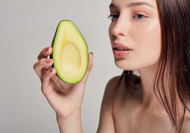 Retrato de uma senhora nua de cabelos castanho com abacate na mão