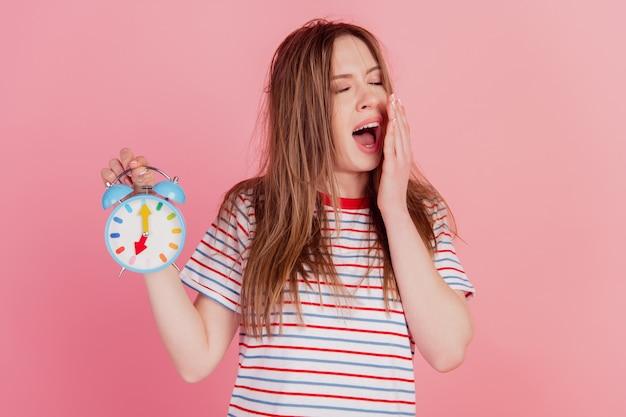 Retrato de uma senhora ruiva sonhadora segurar despertador bocejar fechar olho tampa da palma da mão aberta sobre fundo rosa