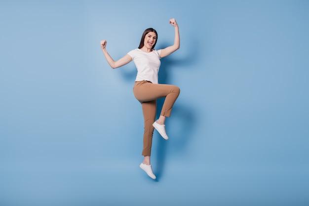 Retrato de uma senhora vencedora animada e alegre, pula e levanta os punhos, celebrando a vitória sobre fundo azul