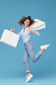 Retrato de uma shopaholic feliz e satisfeita com suas compras, ela pulando contra o fundo azul