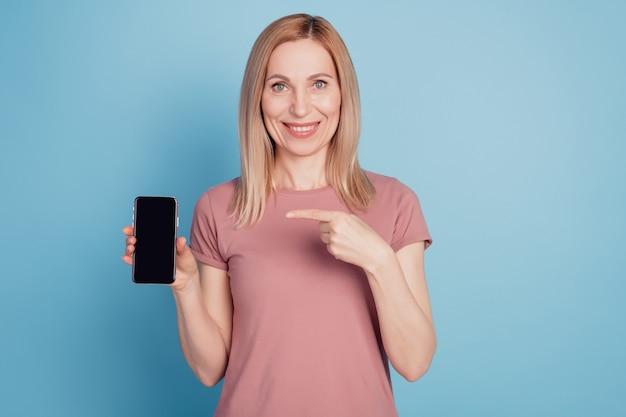 Retrato de uma simpática adorável doce muito atraente encantadora alegre mostrando um novo produto celular isolado sobre fundo azul