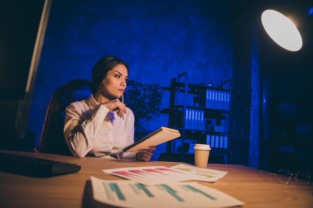 Retrato de uma simpática senhora elegante e habilidosa analista financeiro pesquisando dados analisando relatório dinheiro relação salário resultado juros investir conta auditoria à noite escura estação de trabalho