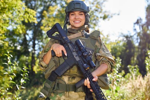 Retrato de uma soldado alegre e sorridente com uma espingarda nas mãos, em um terno militar verde e um chapéu.
