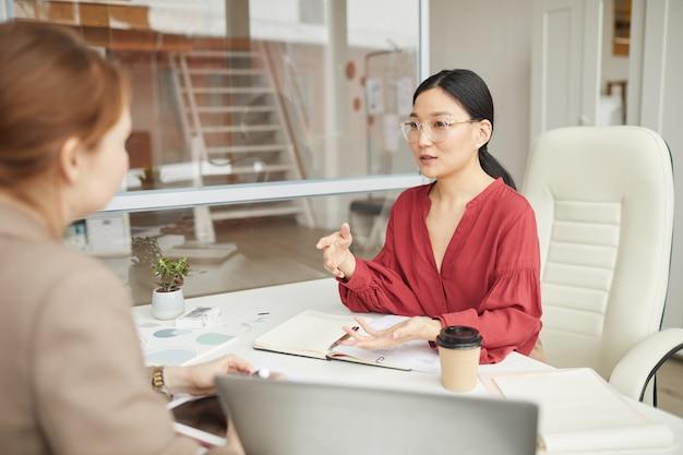 Retrato de uma sorridente empresária asiática falando com o cliente enquanto trabalha na mesa em um cubículo de escritório, copie o espaço