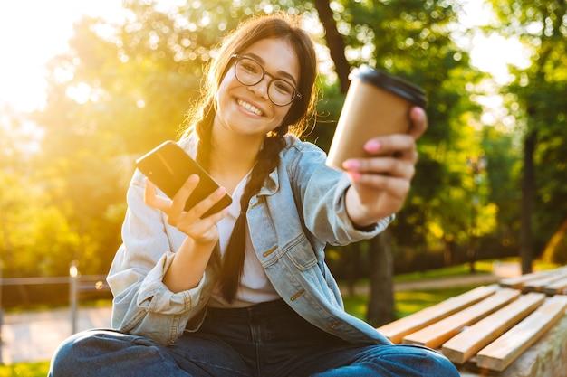 Retrato de uma sorridente jovem estudante jovem usando óculos, sentado ao ar livre no parque natural, usando telefone celular, bebendo café, dá-lhe uma xícara.