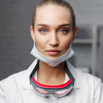 Retrato de uma técnica feminina posando com óculos de segurança