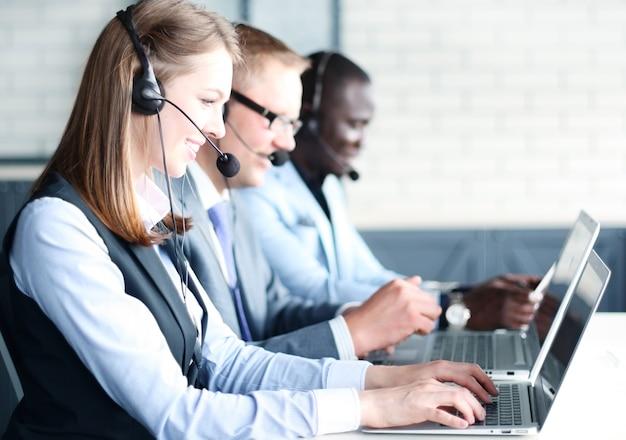 Retrato de uma trabalhadora de call center acompanhada por sua equipe. operador de suporte ao cliente sorridente no trabalho.