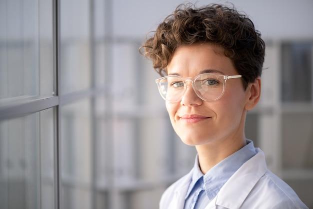 Retrato de uma trabalhadora médica inteligente sorridente de óculos em um laboratório moderno