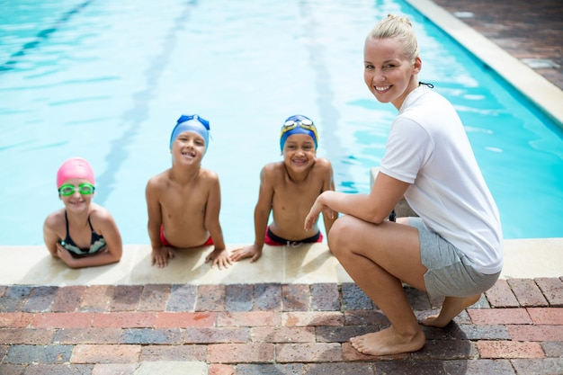 Retrato de uma treinadora de natação ensinando alunos ao lado da piscina