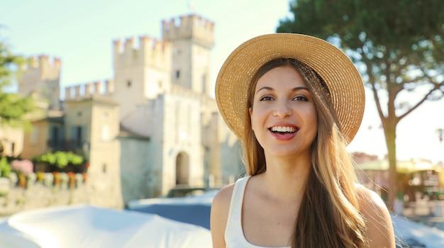 Retrato de uma turista sorridente com o castelo de sirmione ao fundo, lago de garda, itália