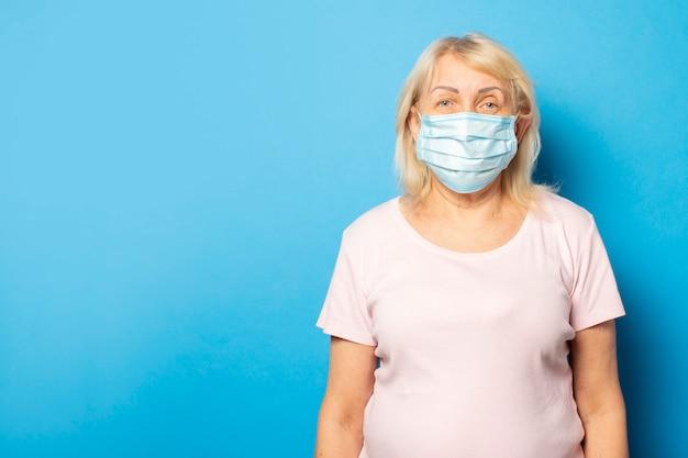 Retrato de uma velha amigável em uma camiseta e máscara protetora médica em uma parede azul isolada. rosto emocional. vírus de conceito, quarentena, ar sujo, pandemia