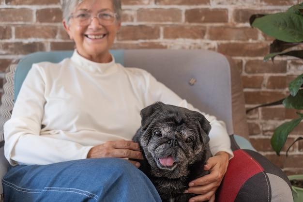 Retrato de uma velha com seu cachorro de estimação, sentado na poltrona na sala de estar. mulher idosa com cachorro em casa. mulher sorridente com um cachorrinho fofo em casa