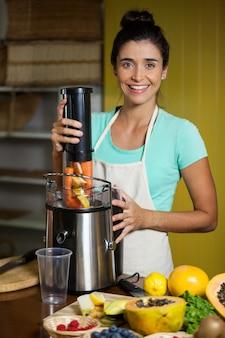 Retrato de uma vendedora sorridente preparando suco