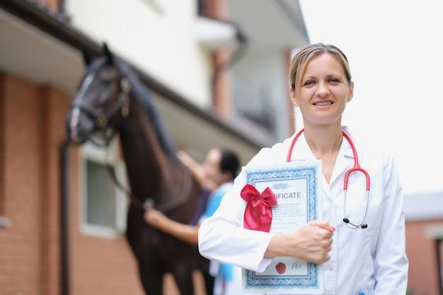Retrato de uma veterinária sorridente segurando um atestado médico no contexto de um cavalo esportivo
