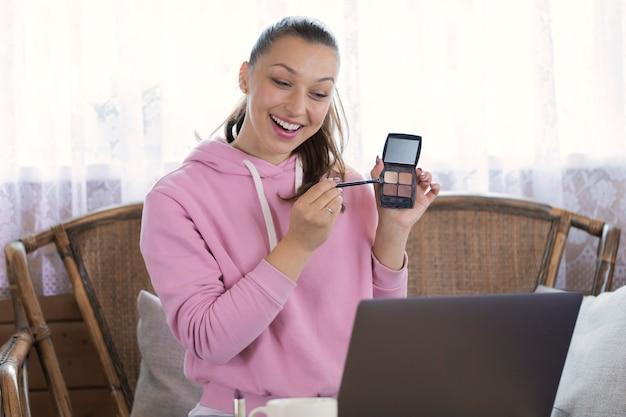 Retrato de uma vlogger linda e sorridente faz revisão de vídeo, usa produtos cosméticos, grava conteúdo útil para blog online