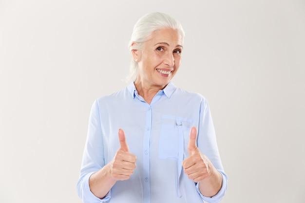 Retrato de velha alegre na camisa azul, mostrando os polegares para cima gesto