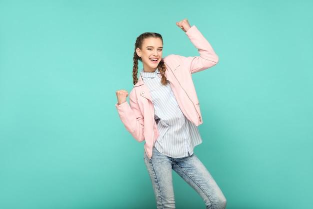 Retrato de vencedor espantado de linda linda garota em pé com maquiagem e penteado pigtail marrom em camisa listrada azul claro jaqueta rosa. indoor, studio shot isolado em fundo azul ou verde.