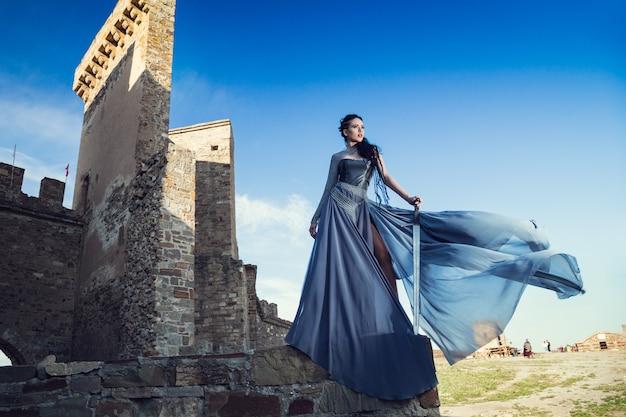 Retrato de verão ao ar livre da bela furiosa guerreira escandinava mulher gengibre em um vestido cinza com cota de malha de metal.