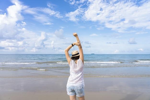 Retrato de verão ao ar livre da jovem mulher asiática usando chapéu elegante e roupas em pé na praia