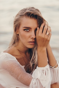 Retrato de verão ao ar livre da linda mulher loira feliz relaxando na praia perto do oceano