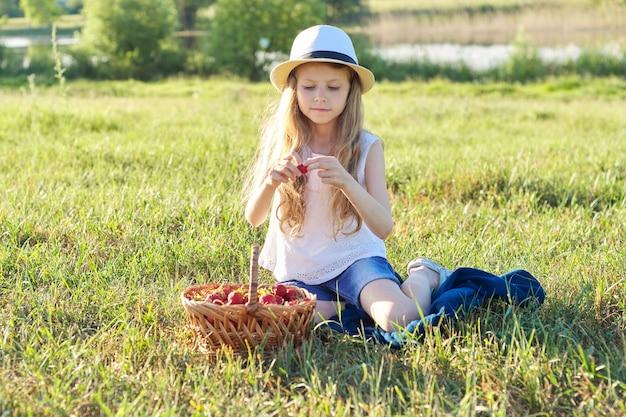 Retrato de verão ao ar livre da menina com cesta de morangos, chapéu de palha. fundo da natureza, paisagem rural, prado verde, estilo country, criança sentada na grama comendo frutas