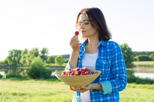 Retrato de verão ao ar livre de mulher adulta com morangos