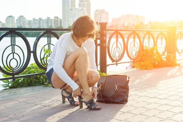 Retrato de verão ao ar livre de mulher madura, endireitar sapatos
