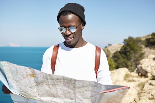 Retrato de verão ao ar livre de um viajante elegante com touca e chapéu, olhando para o mapa nas mãos