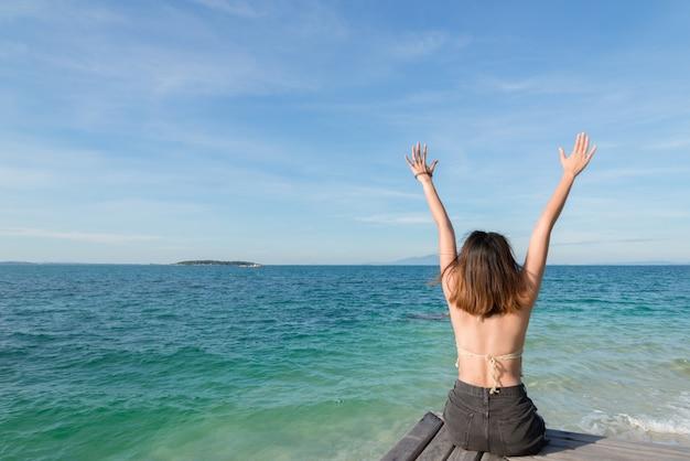 Retrato de verão ao ar livre de uma jovem mulher bonita olhando para o oceano na praia tropical
