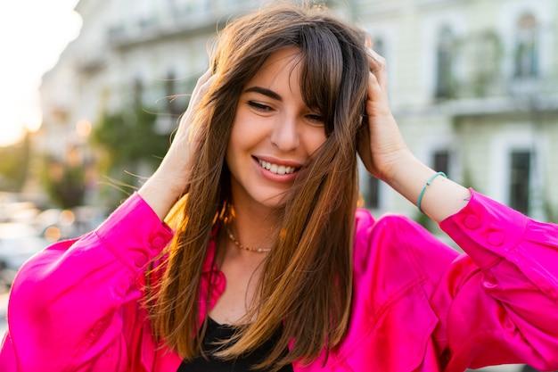 Retrato de verão ao ar livre de uma mulher bonita elegante em uma jaqueta rosa elegante.